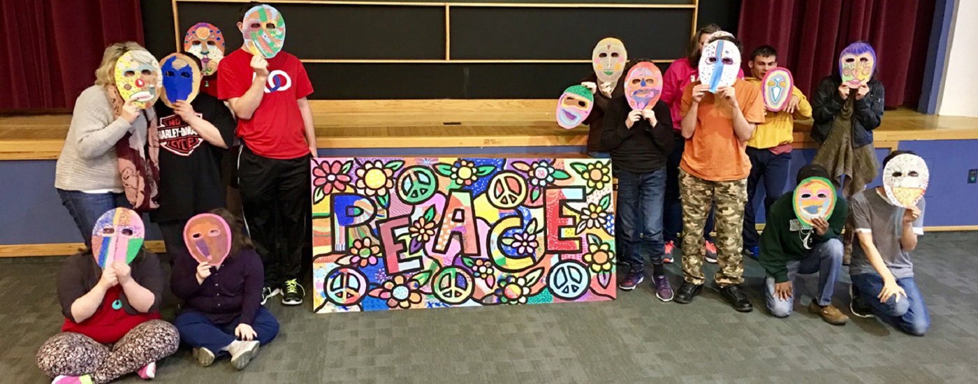 Students with their art masks in front of their faces with their Daniel Cascardo Peace mural in the middle