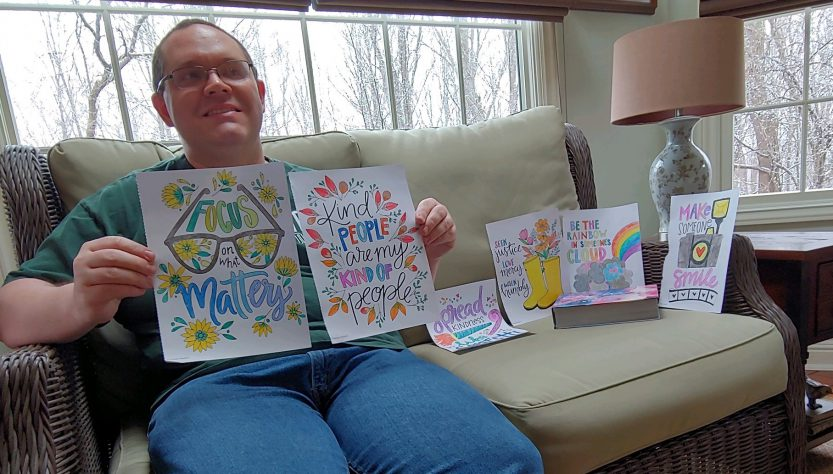 Michael White sitting on his couch holding 2 of his drawings, with several others propped up on the couch next to him.