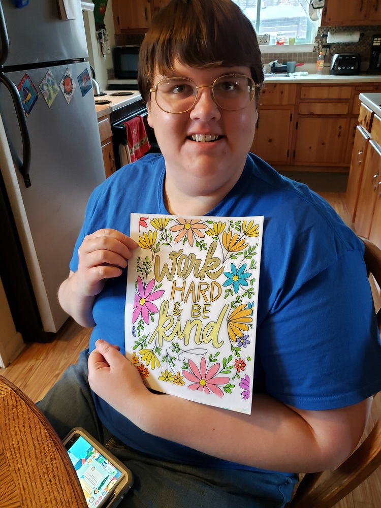 """Club Create member showing """"work hard be kind"""" coloring at home"""