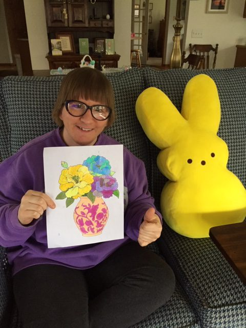 Club Create member showing her beautiful flowers drawing in her living room at home and giving a thumbs up