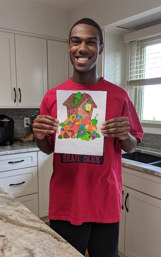 Club Create member with a big smile showing his artwork standing in his kitchen