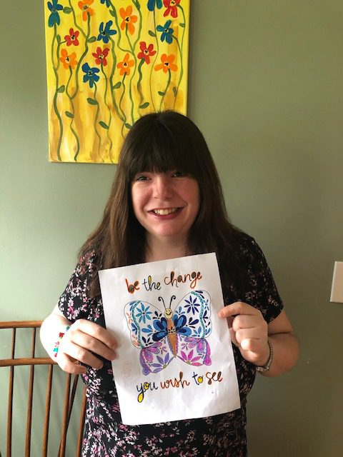 Club Create member showing off her drawing at home