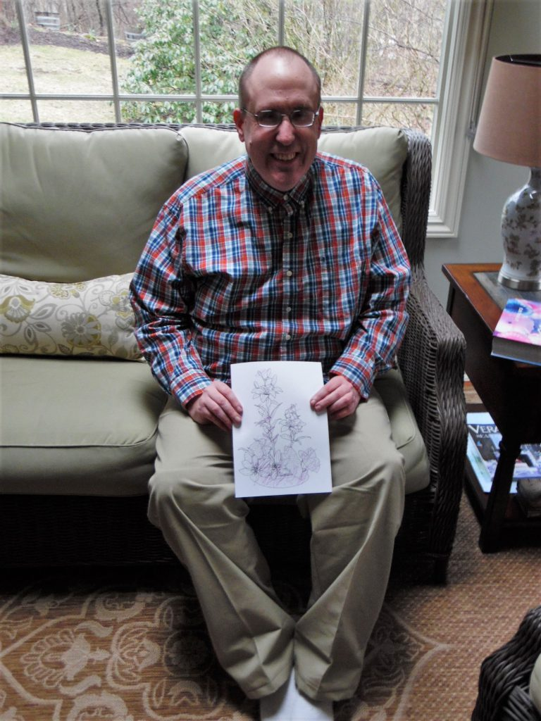 Club Create member showing his drawing in his living room at home