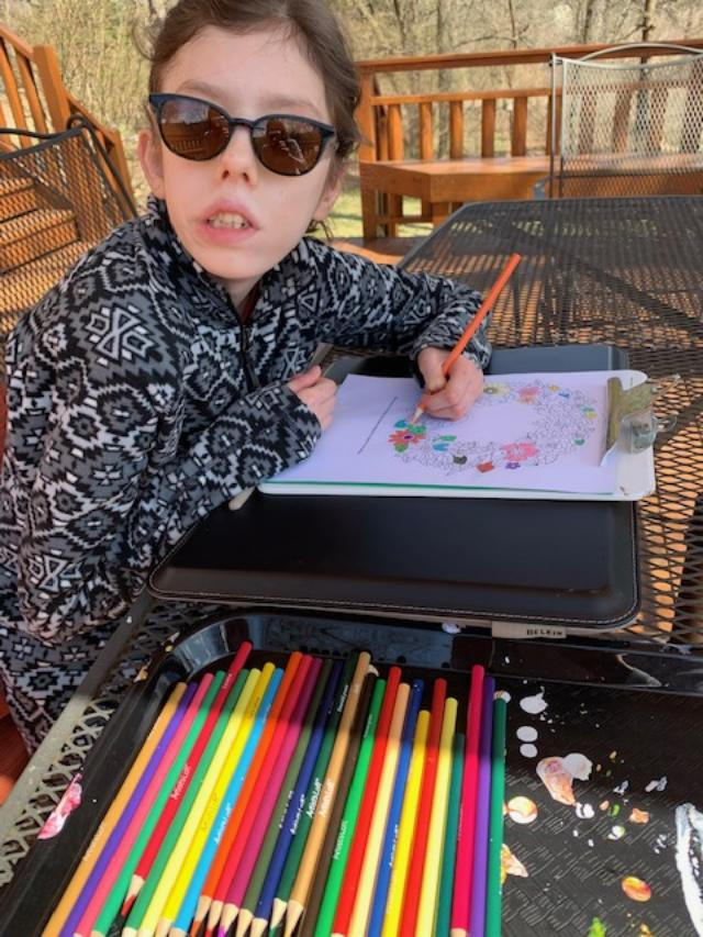 Club Create member using colored pencils on her patio at home