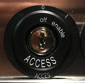 Elevator key hole with small words off and enamble around the edge, and access in capital letters
