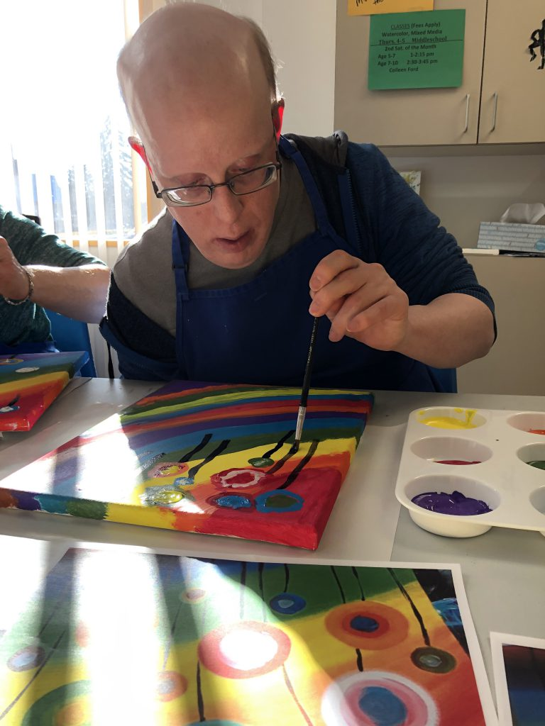 close up of one male Club Create Swartz Creek member carefully working on his painting