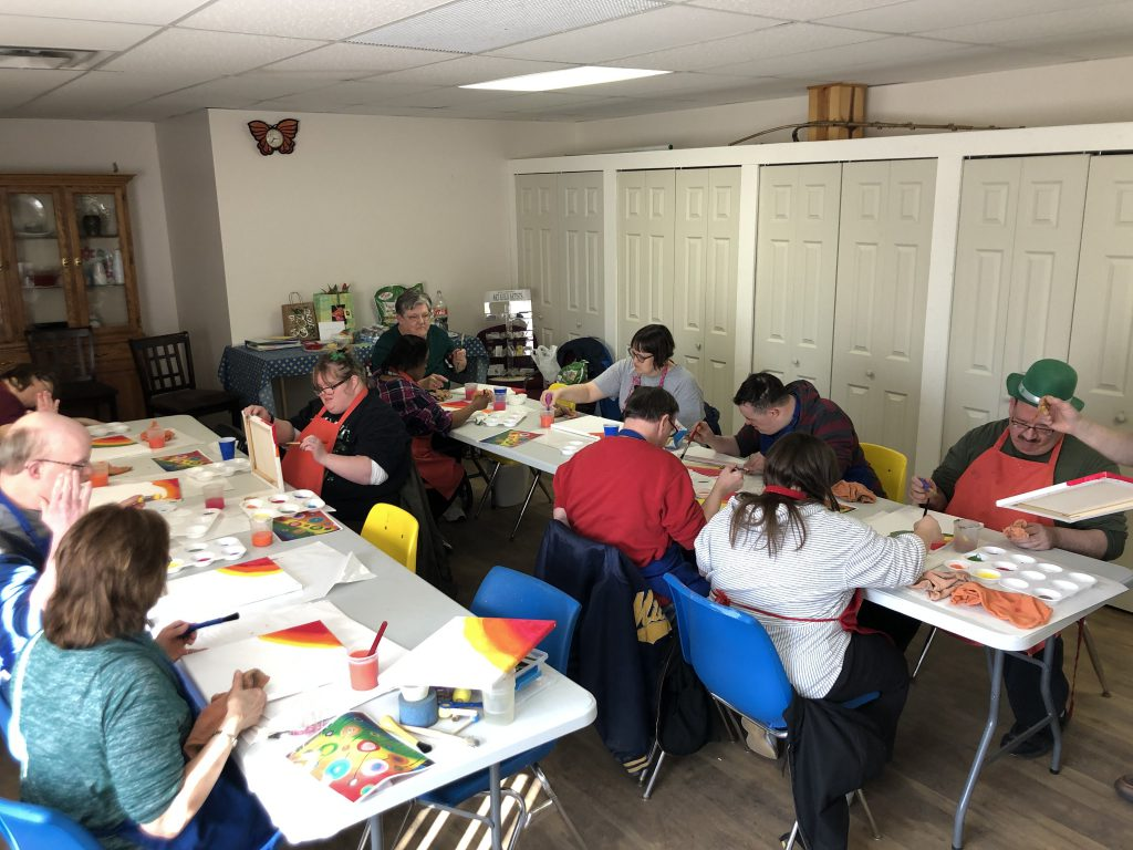 The whole Club Create Swartz Creek membership working on their artwork at two long tables