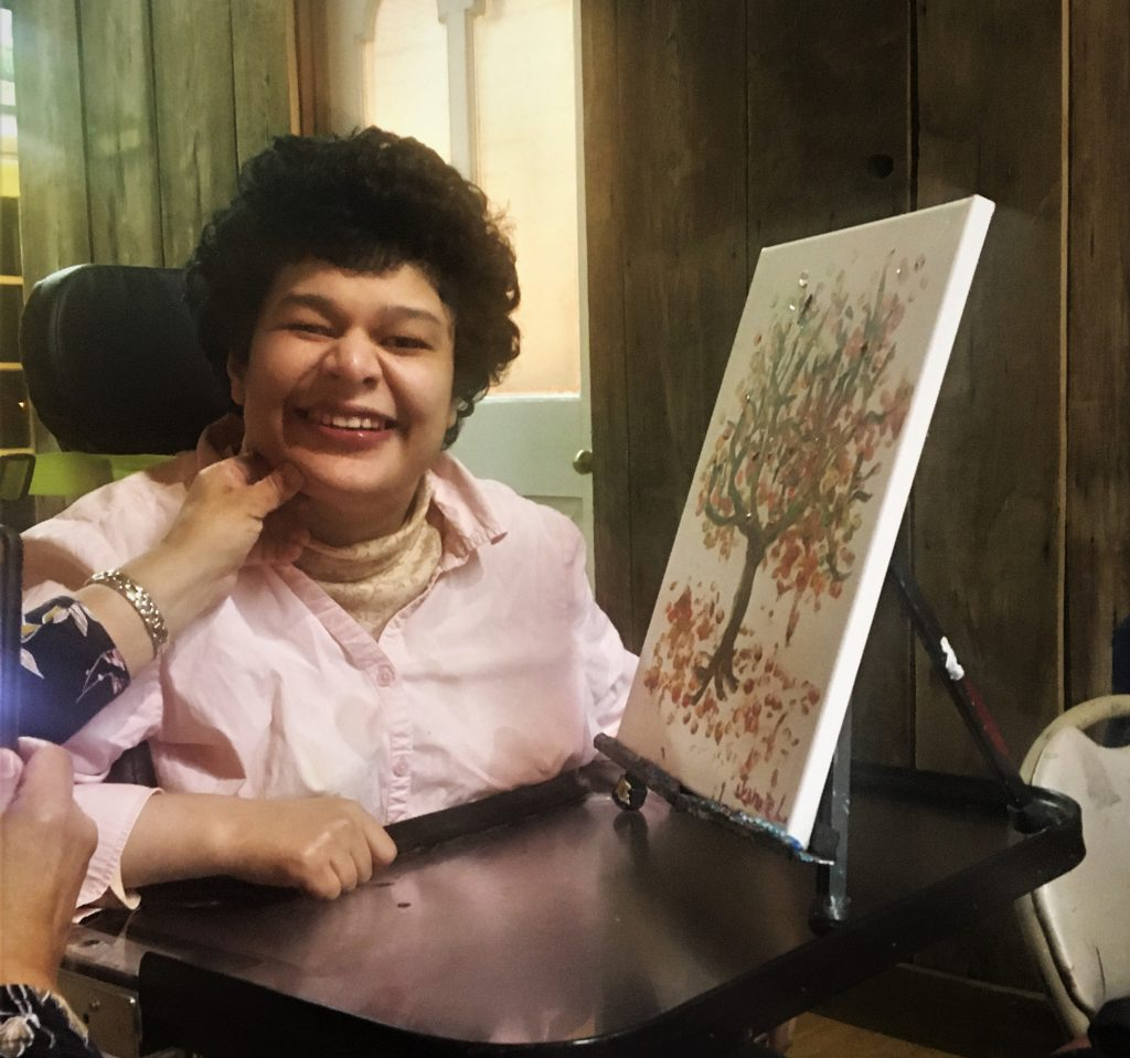 Woman in a wheelchair from Club Create North Oakland County showing her painting with a big smile