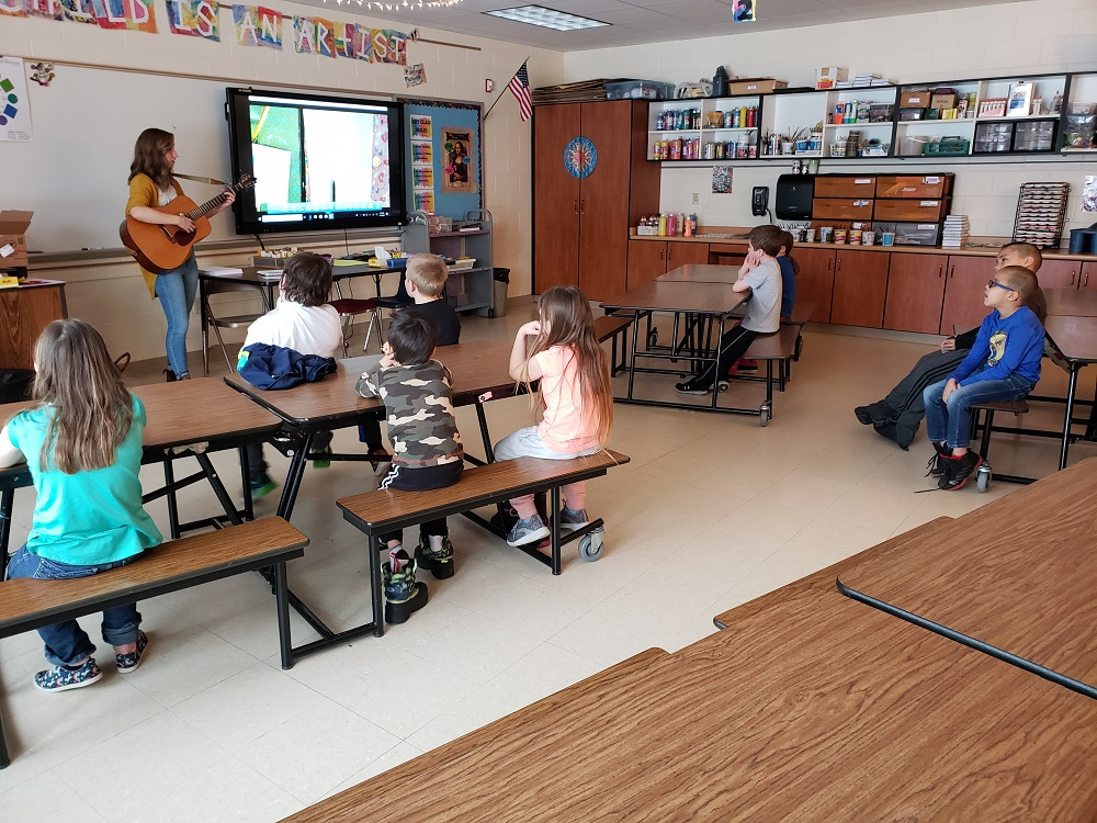 MiAA Teaching Artist Kerry Yost playing her guitar in front of a class of elementary students