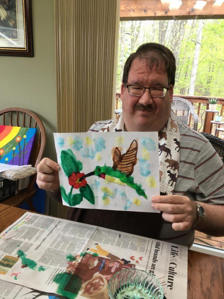 Stephen Broadworth, Club Create Swartz Creek member showing of his hummingbird painting sitting at his kitchen table.