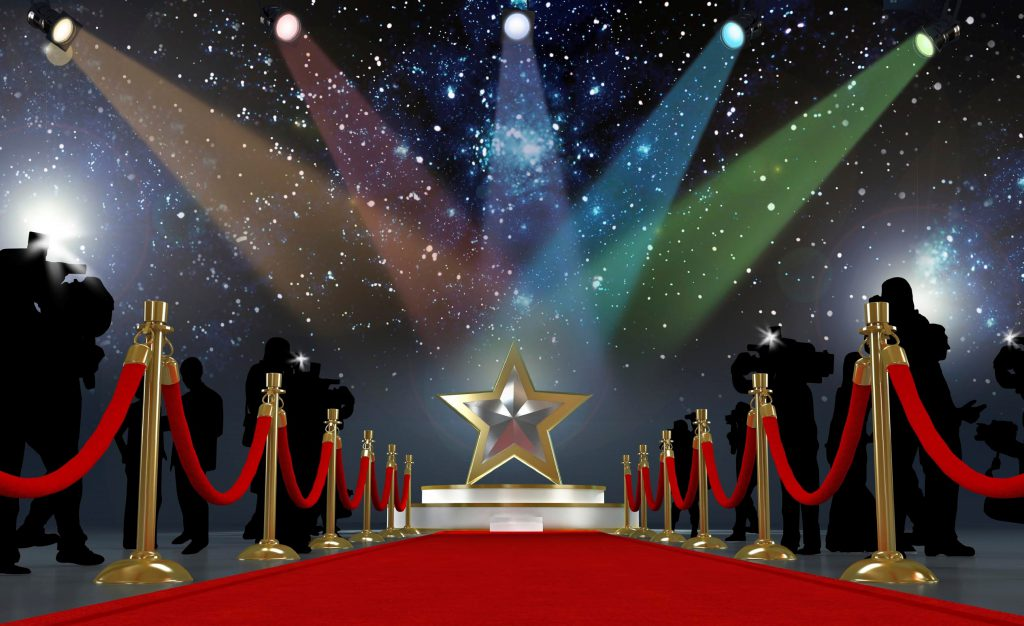A red carpet leading to a platform with a giant gold star standing on it and lights beaming down on it - like Hollywood