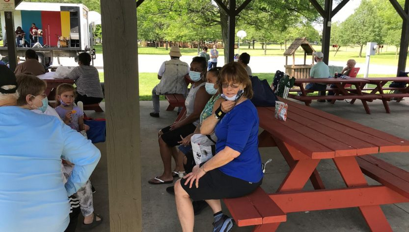 Club Create director, Kathy Cole, and members sitting on picnic tables under an outdoor pavilion listing to live music