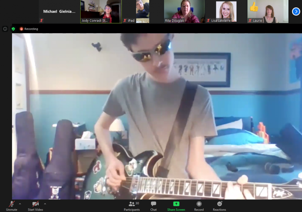 A picture of a client in sunglasses playing electric guitar on camera from his bedroom.