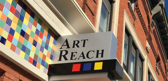 art reach sign on the front of the old downtown building sticking out from a mosaic background on the wall above the door