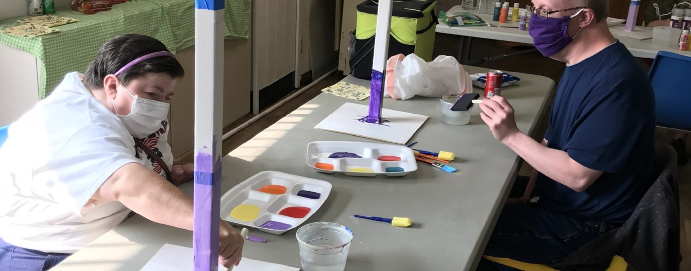 Two club members, a woman in a white shirt wearing a mask, and a man in a blue shirt wearing a mask sit at opposite corners of a table painting their garden totem poles.