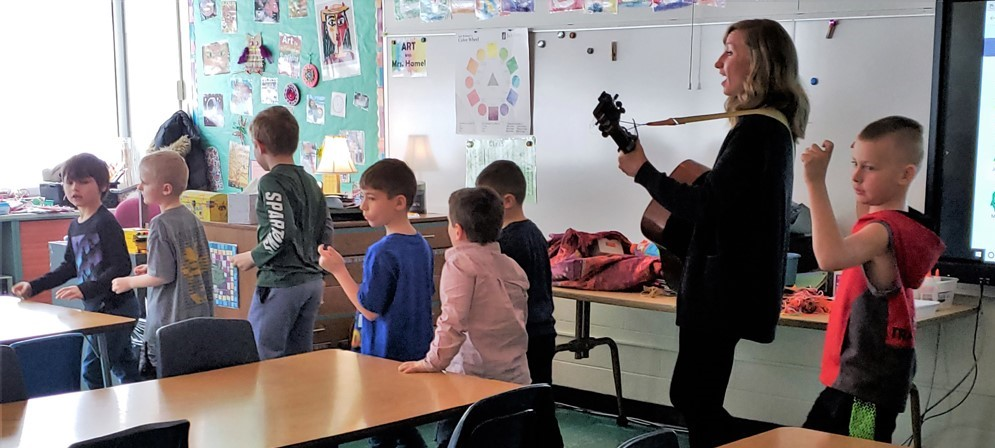 Kerry Yost plays guitar as she marches with young students around the classroom